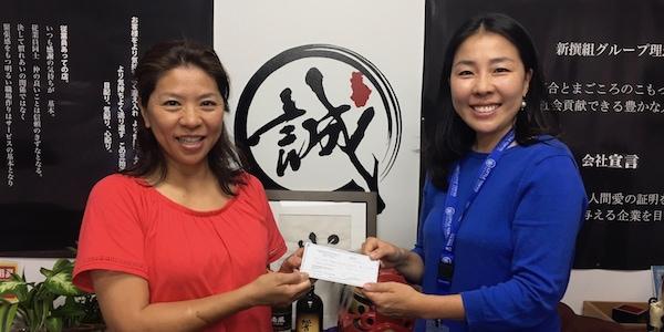 Sayaka Shigeta of Shin-Sen-Gumi presents a check to Hiroko Higuchi of LTSC.
