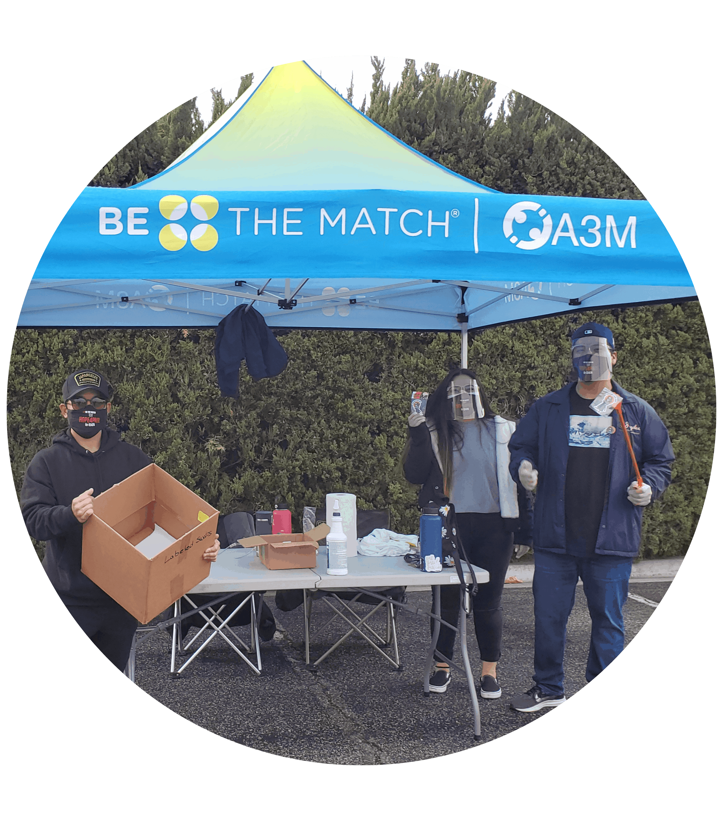 three people under a tent at a drive through swab event