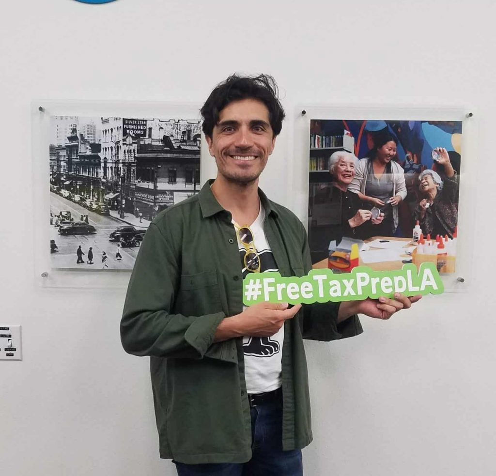 man posing with #freetaxprepla sign in front of LTSC office.