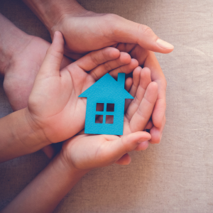 two sets of hands holding cutout of a blue house