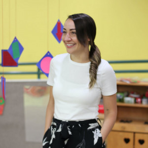 nicole lopez standing in front of yellow wall